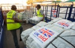 UK Aid Shelter Kits and Water Containers are loaded for shipment