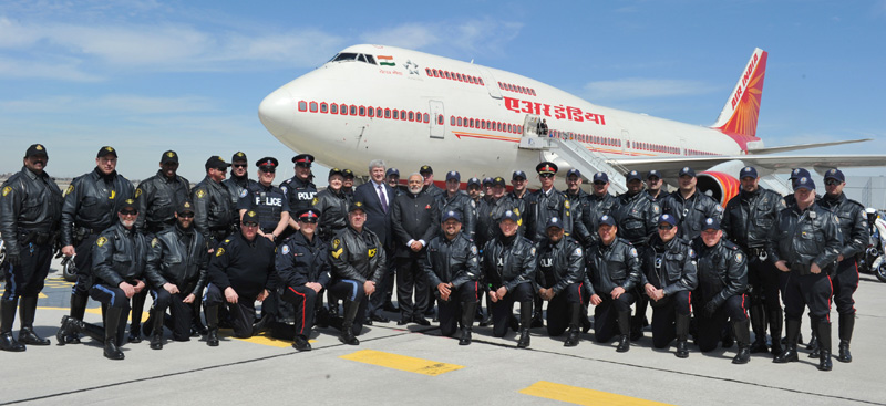 Prime MinisterNarendra Modi in a group photo with the motor cycle riders of Canada Police at the time of PM's departure from Toronto, in Canada on April 16, 2015.  Prime Minister of Canada Stephen Harper is also seen.